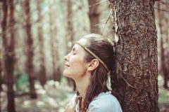 Eine Frau steht zwischen Bäumen stockbilder