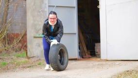 Eine Frau stellt einen Autoreifen mit einer Diskette aus der Garage heraus bereit stock video footage