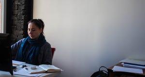 Eine Frau am Tisch, der am Computer arbeitet lizenzfreies stockbild