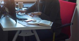 Eine Frau am Tisch, der am Computer arbeitet stockfoto