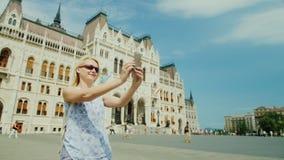 Eine Frau touristische Fotografien selbst vor dem hintergrund des ungarischen Parlaments Tourismus in Europa stock footage