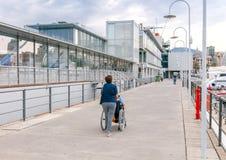 Eine Frau trägt einen Behinderter in einem Rollstuhl lizenzfreie stockfotografie
