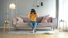 Eine Frau trägt VR-Gläser bei der Kontrolle eines Roboterstaubsaugers stock video footage