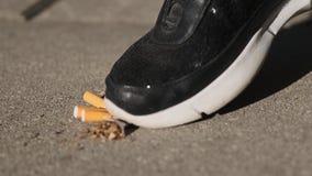 Eine Frau trampelt Zigaretten auf Asphalt, aufhören zu rauchen, beendigte zu rauchen stock video footage