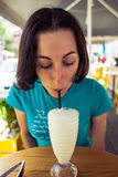 Eine Frau trinkt ein Milchshaken lizenzfreies stockfoto