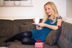 Eine Frau trinkt eine Tasse Tee Stockbild