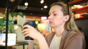 Eine Frau trinkt Kaffee an einem Schnellimbisscafé Wegwerfbares Cup Kaffee zum zu gehen stock footage