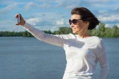 Eine Frau tut selfie unter Verwendung des Smartphone Blauer Himmel des Hintergrundes mit Wolken, Fluss Lizenzfreie Stockfotografie