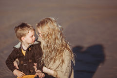 Eine Frau umfasst ihren Sohn, der sie betrachtet Stockfoto