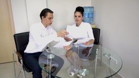 Eine Frau und ein junger Mann besprechen Projekte an Ihrem Schreibtisch im Büro Lizenzfreies Stockbild