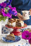 Eine Frau und ein Kuchen von dünnen Pfannkuchen mit weißer Creme und Nüssen Milchmann mit Blumen in den Händen des Mädchens Frisc lizenzfreies stockfoto