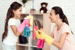 Eine Frau und ein Mädchen werfen mit Geld für das Säubern der Wohnung auf Sie sind zu Hause Stockbilder