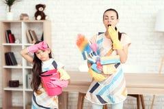 Eine Frau und ein Mädchen werfen mit Geld für das Säubern der Wohnung auf Sie sind zu Hause Stockfotografie