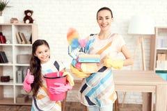 Eine Frau und ein Mädchen werfen mit Geld für das Säubern der Wohnung auf Sie sind zu Hause Lizenzfreie Stockfotos