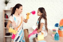Eine Frau und ein Mädchen werfen mit Geld für das Säubern der Wohnung auf Sie sind zu Hause Lizenzfreie Stockfotografie