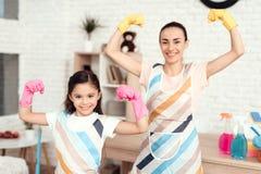 Eine Frau und ein Mädchen werfen mit Geld für das Säubern der Wohnung auf Sie sind zu Hause stockfotos