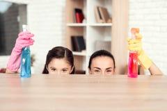 Eine Frau und ein Mädchen werfen mit Geld für das Säubern der Wohnung auf Sie sind zu Hause Stockfoto