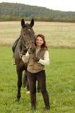Eine Frau und ein Pferd auf einem Feld. Stockbild