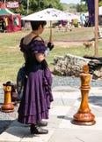 Eine Frau und riesigen Schachfiguren am Renaissance-Festival Stockfotografie