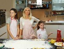 Eine Frau und zwei Mädchen, die Teig machen Stockbilder