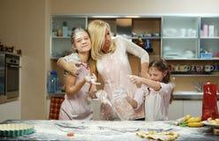 Eine Frau und zwei Mädchen, die Teig machen Lizenzfreies Stockbild