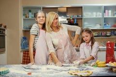 Eine Frau und zwei Mädchen, die Teig machen Lizenzfreie Stockfotos