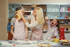 Eine Frau und zwei Mädchen, die Teig machen Lizenzfreies Stockfoto