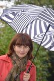 Eine Frau unter einem Regenschirm im Regen Stockfotos