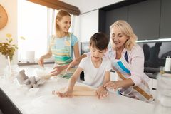 Eine Frau unterrichtet ihren Sohn, selbst gemachte Kuchen zu kochen Ihre Mutter hilft ihr Der Junge rollt den Teig mit einem Nude lizenzfreies stockfoto