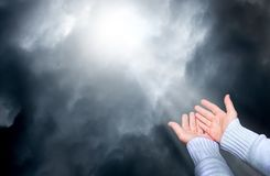 Eine Frau verlängert ihre Hände im Gebet auf den Himmel, von dem durch die dunklen Wolken Strahl von light_ schaut lizenzfreie stockfotografie