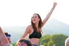 Eine Frau von der Menge, die in einem Tageslichtkonzert an FLUNKEREI Festival zujubelt Lizenzfreies Stockfoto