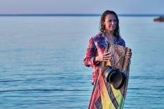 Eine Frau von mittlerem Alter hat das Wakesurfing auf einem großen Fluss an einem Sommerabend beendet lizenzfreies stockfoto