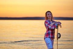 Eine Frau von mittlerem Alter hat das Wakesurfing auf einem großen Fluss an einem Sommerabend beendet stockbilder