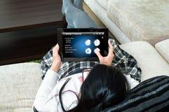 Eine Frau wählt Art der Aktion auf applica das smarthome der Tablette Stockfotografie