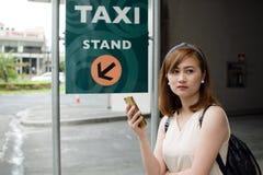 Eine Frau wartet auf ein Fahrerhaus Stockfotografie