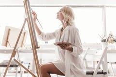 Eine Frau zeichnet ein Bild auf dem Gestell Stockfotos