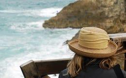 Eine Frauen-überwachende Wellen brechen über Felsen auf Strand ab Lizenzfreies Stockfoto