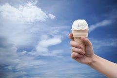 Eine Frauenhand, die Eistüte mit blauem Himmel und Wolken des Sommers im Hintergrund, bunte Bildart hält Lizenzfreies Stockbild