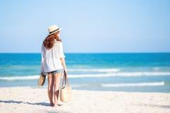 Eine Frauenholdingtasche und -schuhe beim Schlendern auf den Strand lizenzfreie stockfotografie