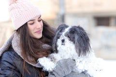 Eine Freundschaft zwischen einem lächelnden Mädchen und einem kleinen Schoßhund stockbild