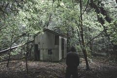 Eine furchtsame mit Kapuze Zahl Stellung in einem gespenstischen Wald nahe bei einer ruinierten Hütte Mit gedämpft unheimlich red lizenzfreies stockbild