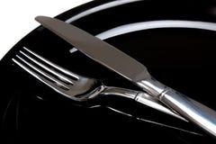 Eine Gabel und ein Messer auf einer schwarzen Platte Stockbild