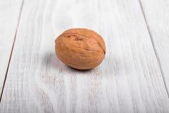 Eine ganze Walnuss auf hölzernem Hintergrund, gesunde Gehirnnahrung, Walnuss auf heller Weinlesetabelle lizenzfreies stockfoto