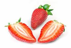 Eine ganzen und zwei geschnittenen Erdbeeren Lizenzfreies Stockbild