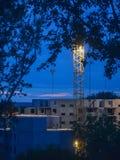 Eine Gebäudeansicht im Bau und der Kran in der Dämmerung durch die Niederlassungen von Bäumen stockfotos