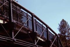 Eine gebogene Eisenbrücke über einem Park lizenzfreie stockfotos