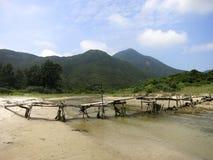 Eine gebrechliche Brücke über einem Nebenfluss am Strand Stockfotos
