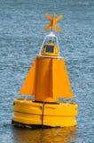 Eine gelbe Boje, die auf die Wasseroberfläche schwimmt Lizenzfreies Stockbild