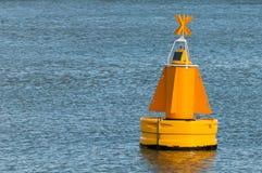 Eine gelbe Boje, die auf die Wasseroberfläche schwimmt Stockfotografie