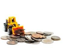 Eine gelbe Spielzeugplanierraupe mit Stapel Münzen auf weißem Hintergrund lizenzfreie stockfotografie